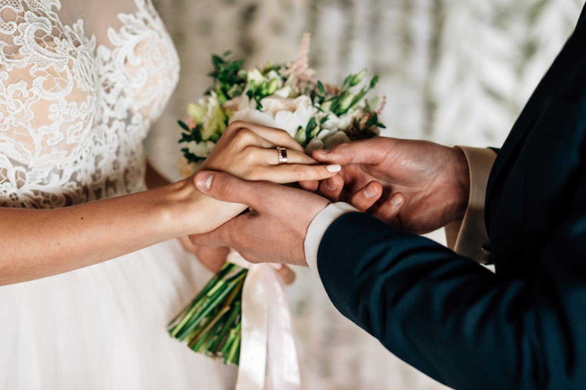 bride and groom placing ring on fingers